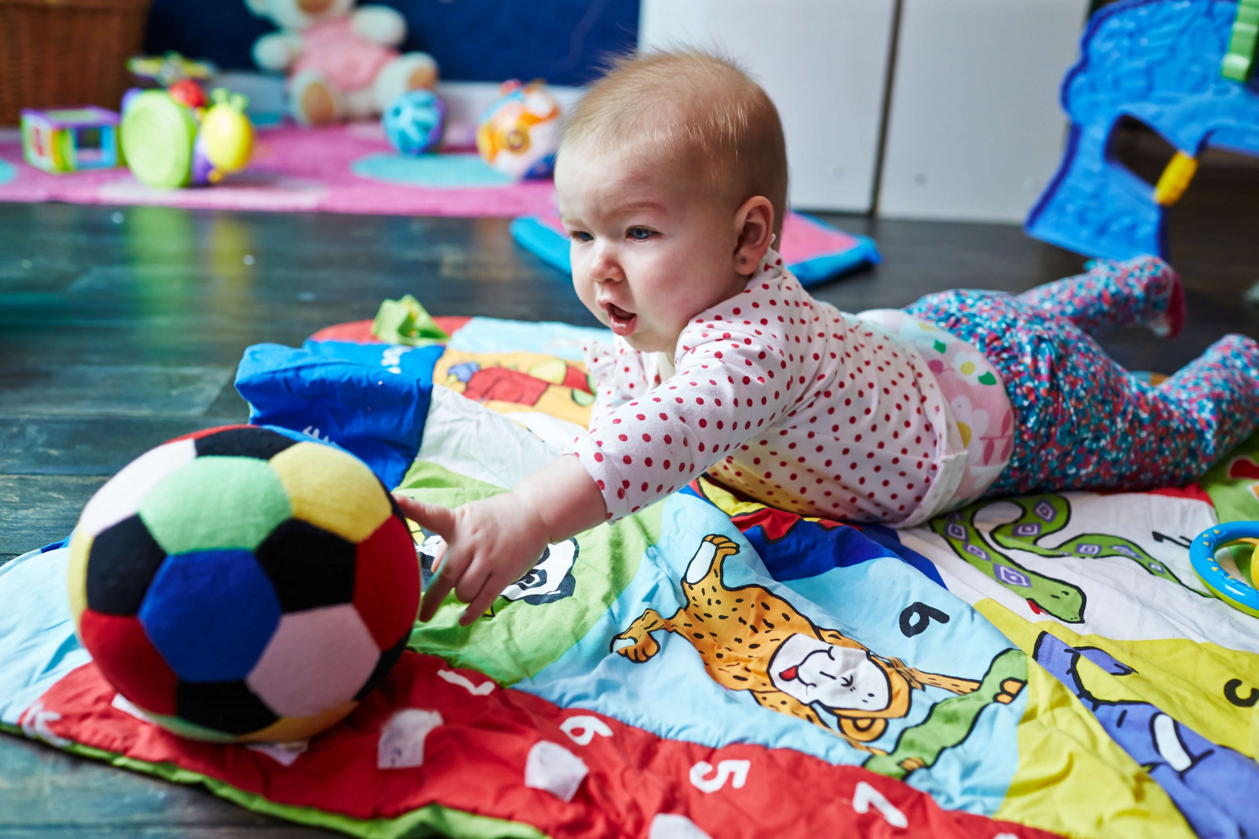 Baby reaching for ball during tummy time