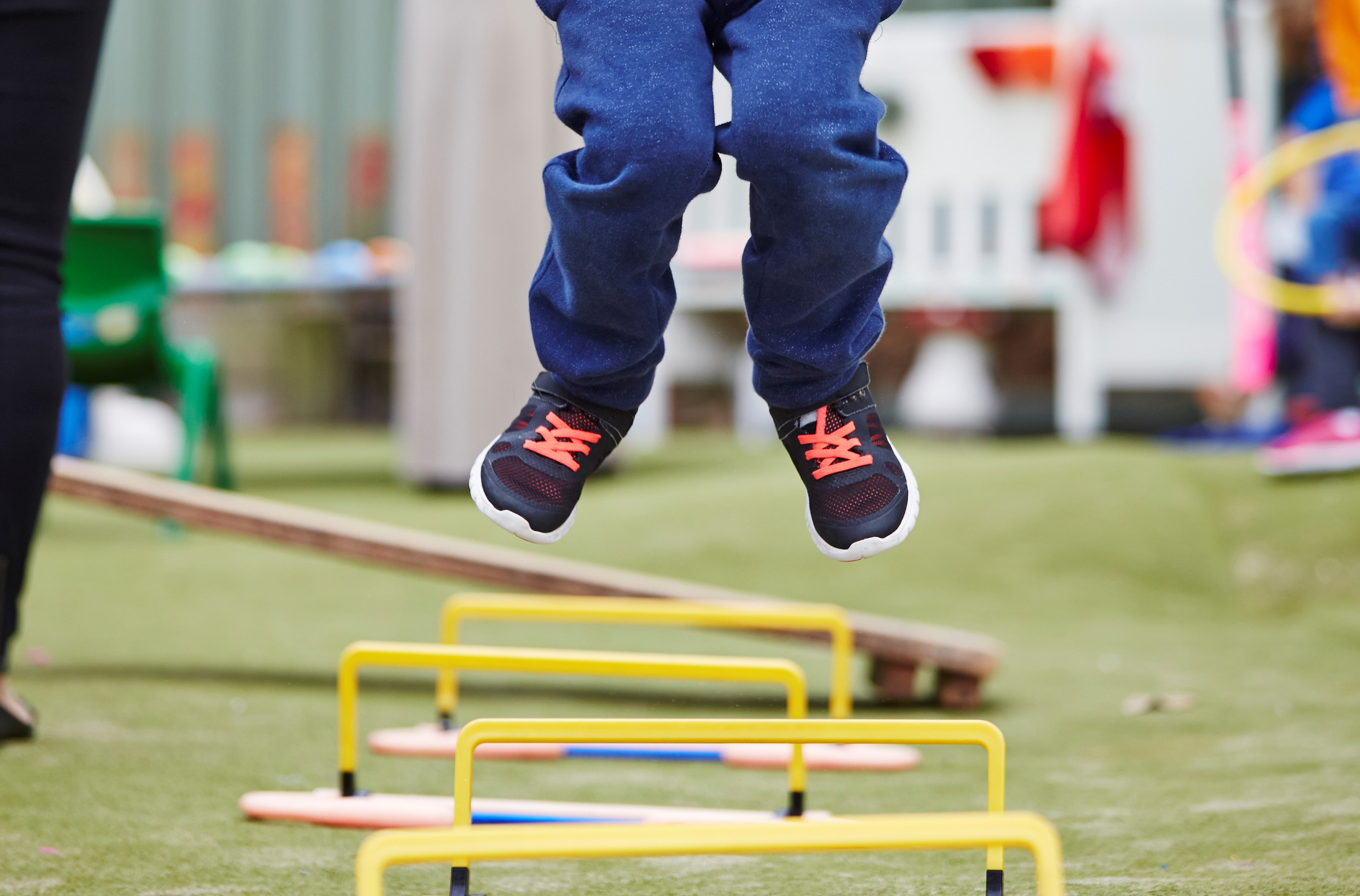 Young boy leaping over obstacle course