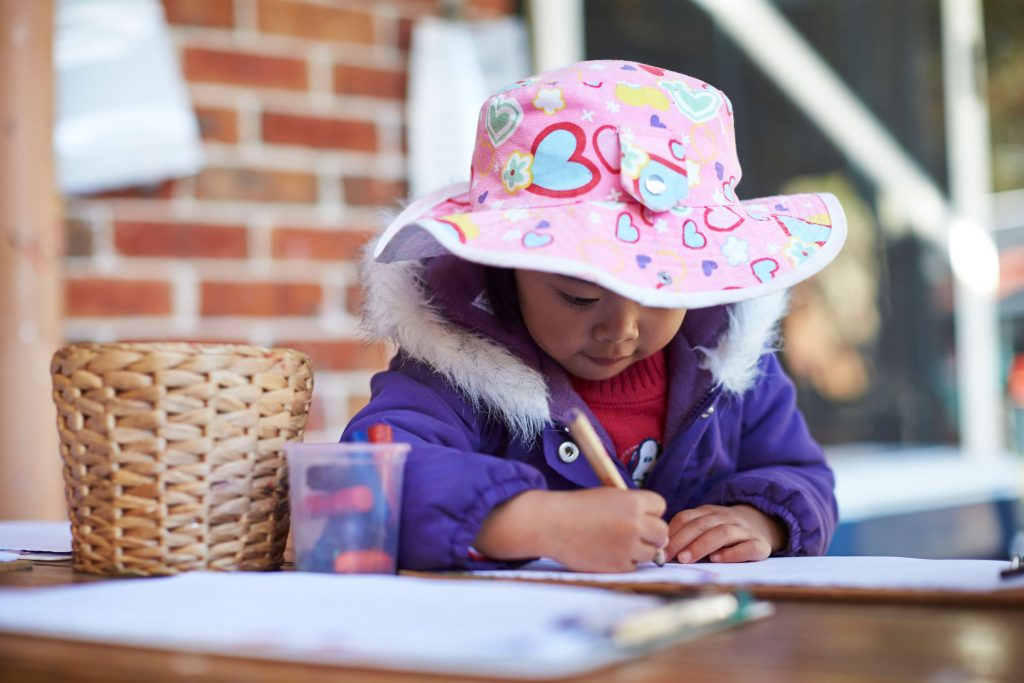 Girl in hat writes at table