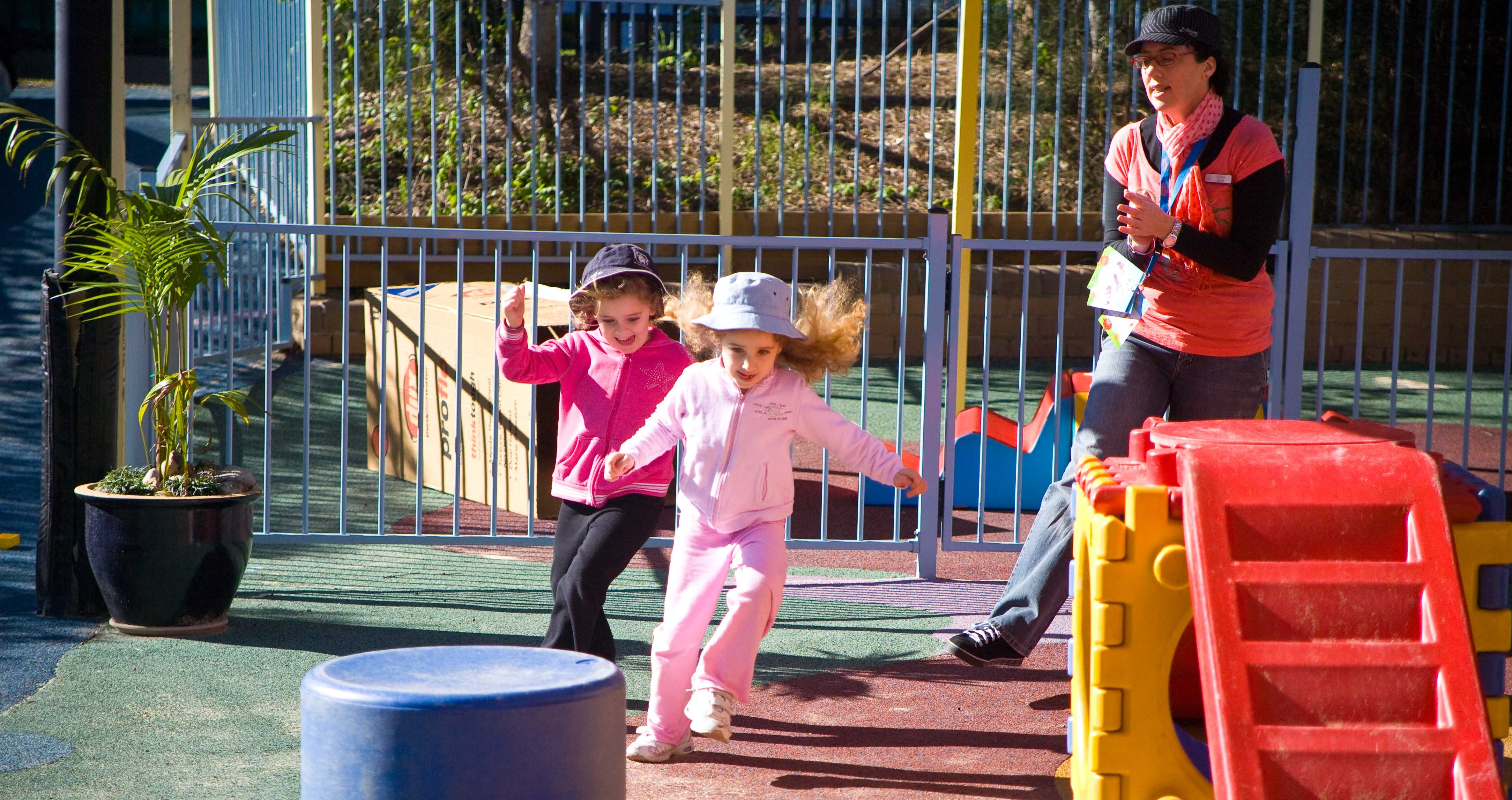 Two children complete an obstacle course with support from an early childhood educator