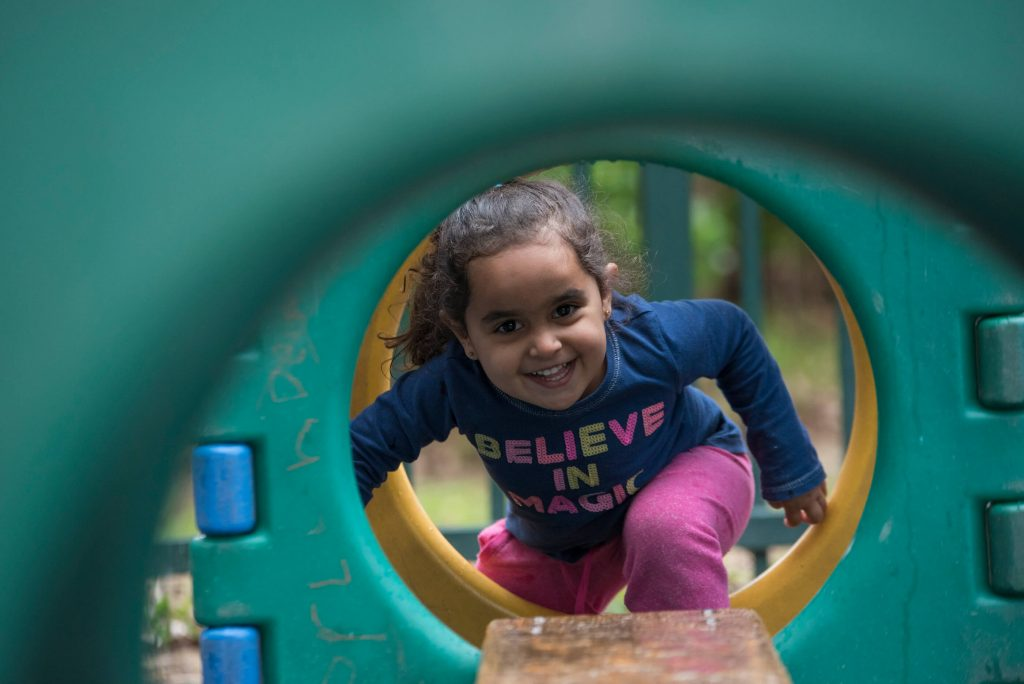Girl looks through play equipment and smiles