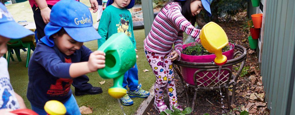 Children watering garden with watering cans
