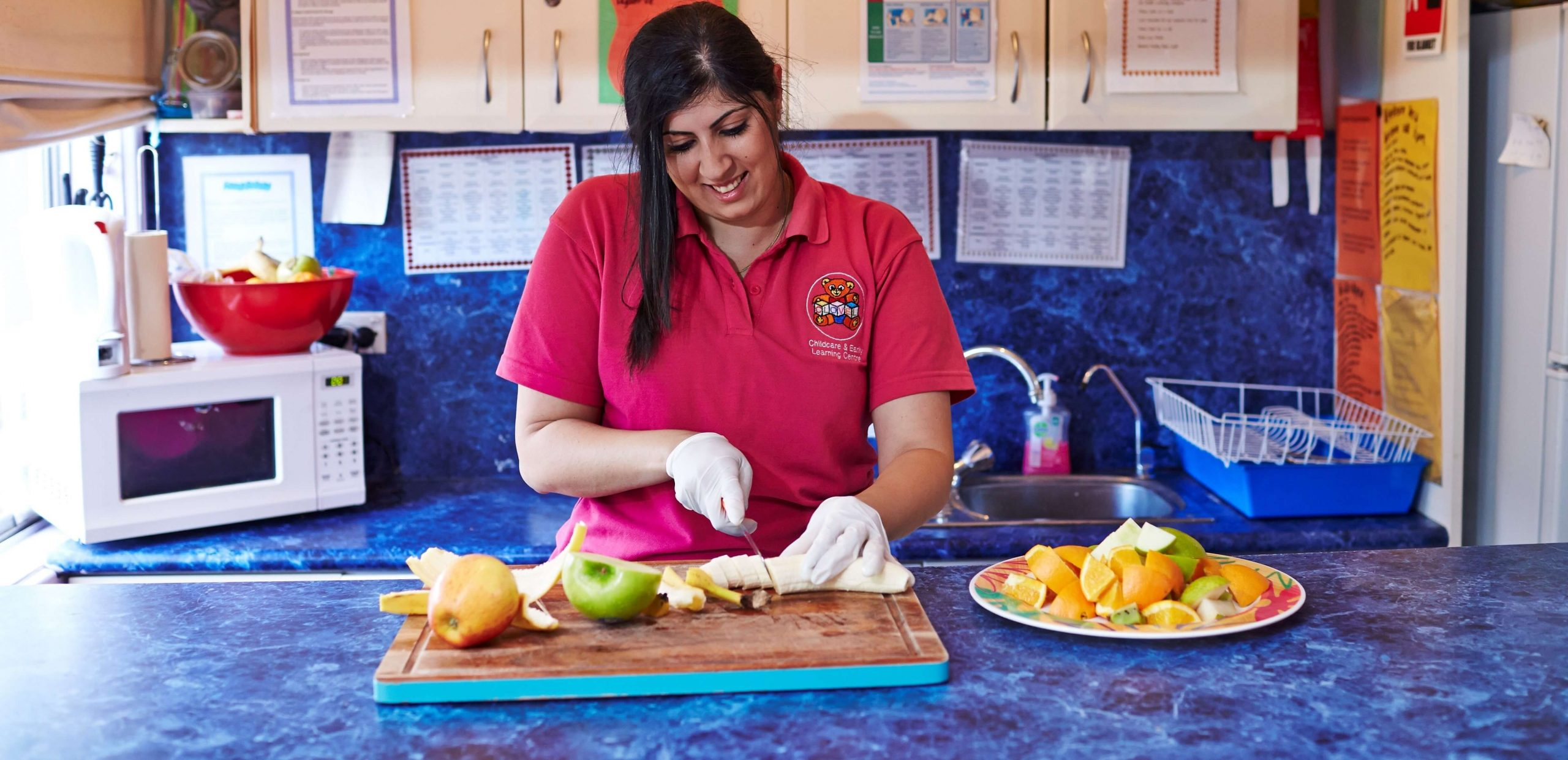 Early childhood educator cutting fruit on a chopping board